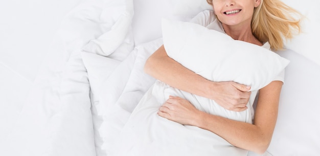Close-up pretty mature woman holding her pillow