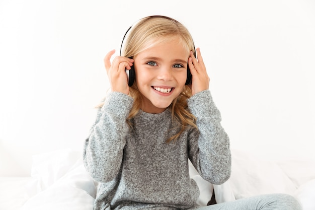 Close-up of pretty smiling little girl touching her headphones while listening to music,