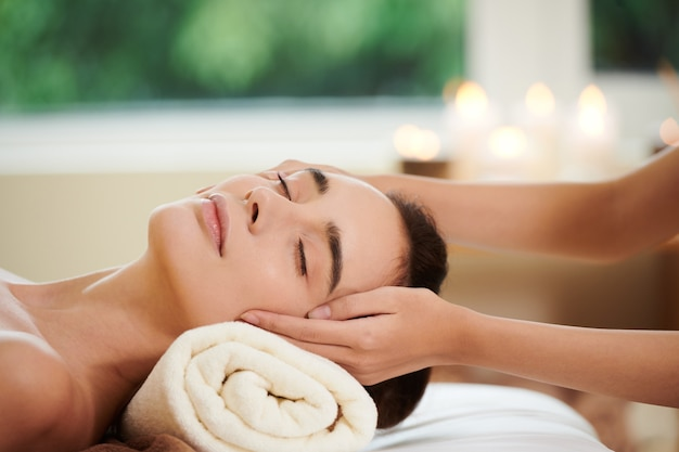 Close-up of pretty woman lying on bed and getting massage from therapist