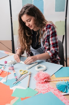Close-up of pretty woman making craft using white clay