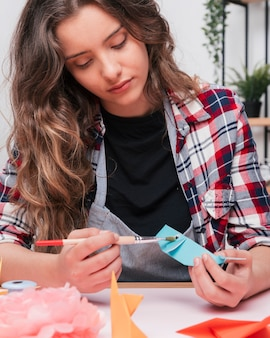 Close-up of pretty woman painting a origami paper fish