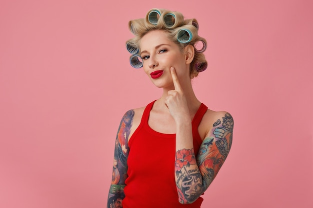 Close-up of pretty young blonde tattooed female with curlers on her head and red lips looking cunningly at camera and smiling slightly, dressed in casual clothes while standing over pink background