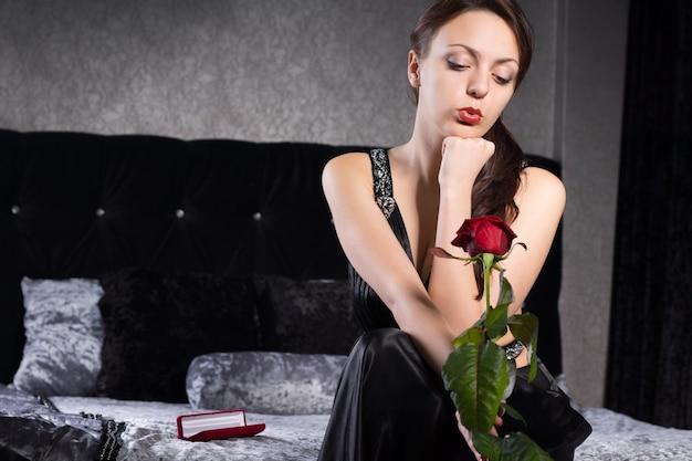 Закройте симпатичную молодую женщину в черном платье, ожидая чего-то, держа цветок красной розы.