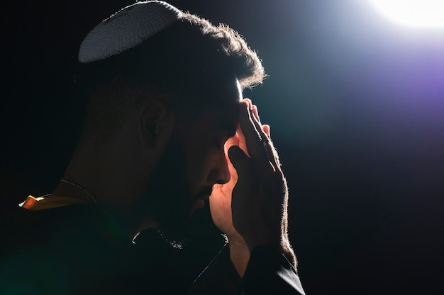 Close-up priest praying on full moon