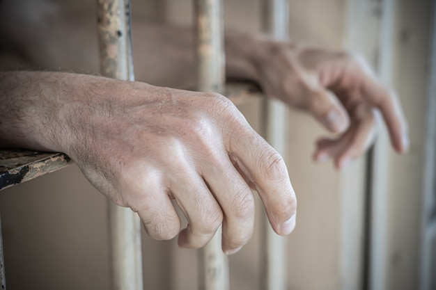 Close up of prisoner hands in a jail
