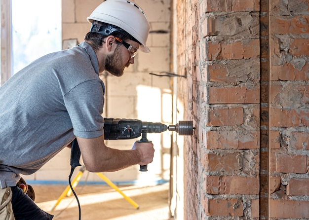 Close-up of the process of drilling a brick wall at a construction site.