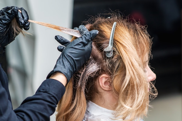 Close up process of dyeing woman's hair at beauty salon.