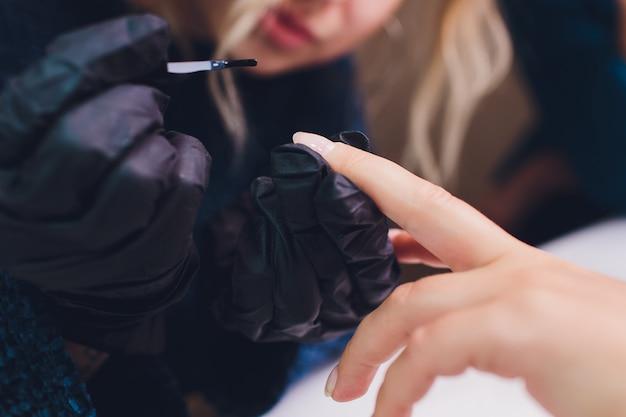Close up of process france manicure at beauty salon.