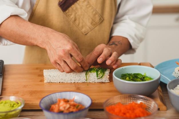 연어 생선과 흰 쌀로 롤링 스시 롤을 준비하는 과정을 닫습니다