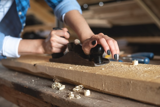 Close-up of the process of planing a wooden bar with a hand planer by women's hands