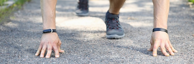 Close-up of professional athlete preparing for run in park. man in comfy stylish grey sneakers in position.