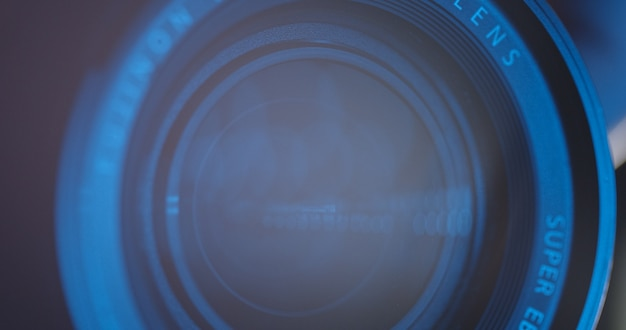 Close-up of a professional camera lens in a studio on a dark background. professional video or photo camera. camcorder lens. adjusting camera lens aperture. news. copy space. graphics. television.