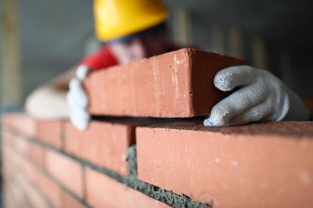 Close-up of professional construction worker laying bricks in industrial site. builder in protective uniform. man building wall with blocks. renovation concept