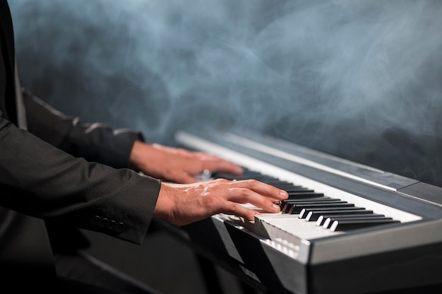 Close-up professional keyboard player and smoke