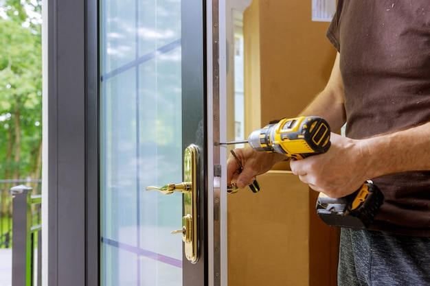 Close up of a professional locksmith installing or repairing a new deadbolt lock