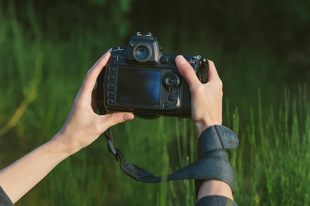 Close-up, professional photo-video camera in the hands of a girl. against the background of green nature and forest.