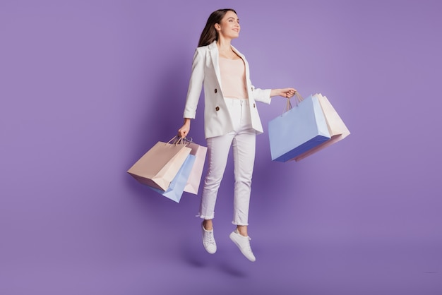 Close up profile portrait of charming shopaholic active lady hold many shop bags jump up on purple wall