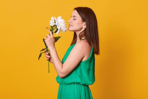 Close up profile portrait of lady wearing green sundress keeps flowers in hands on yellow, being happy to recive peonies as gift.