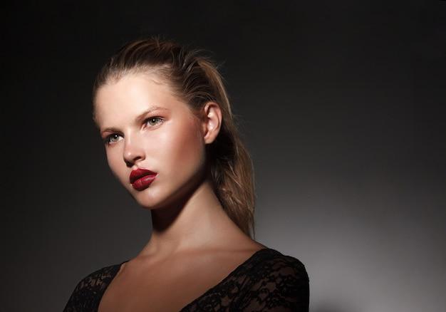 暗い灰色の背景に、ポニーテールに髪を集めた美しい金髪の若い女性モデルの横顔の肖像画を閉じます。