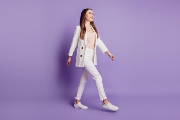 Крупным планом портрет очаровательной милой дамы гулять смотреть пустое пространство носить формальный костюм позирует на фиолетовой стене