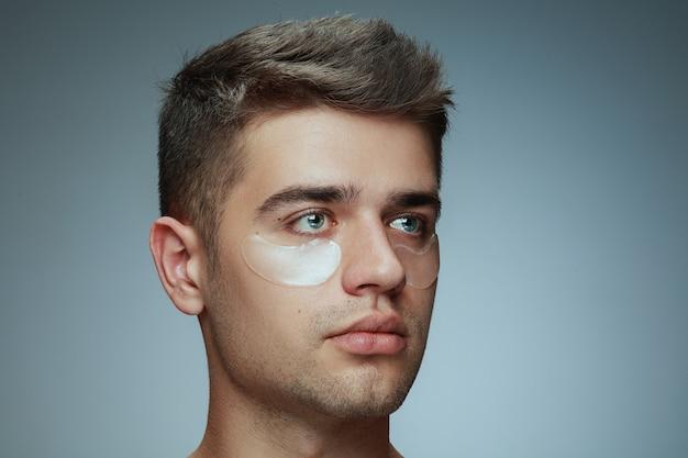 회색 배경에 고립 된 젊은 남자의 클로즈업 프로필 초상화. 눈 아래 콜라겐 패치가있는 남성 얼굴.