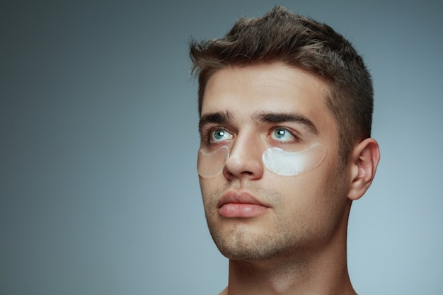 회색 스튜디오 배경에 고립 된 젊은 남자의 클로즈업 프로필 초상화. 눈 아래 콜라겐 패치가있는 남성 얼굴. 남성의 건강과 미용, 미용, 신체 및 피부 관리의 개념. 노화 방지.
