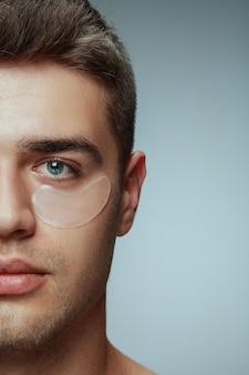灰色のスタジオの背景に分離された若い男のクローズアッププロフィールの肖像画。目の下にコラーゲンパッチがある男性の顔。男性の健康と美容、美容、ボディケア、スキンケアのコンセプト。老化防止。
