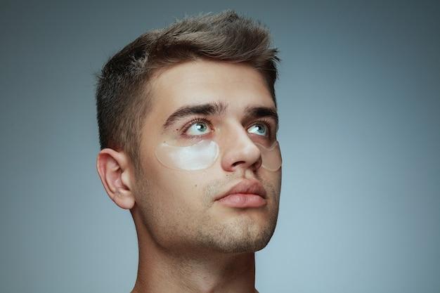 회색 스튜디오에 고립 된 젊은 남자의 클로즈업 프로필 초상화