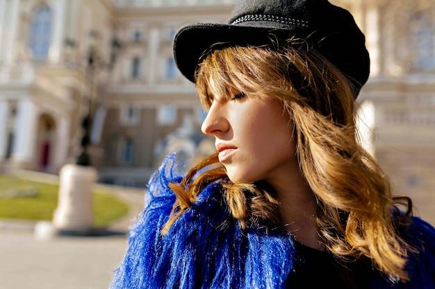 Close up ritratto di profilo al di fuori della donna tenera in berretto nero e cappotto blu, godersi il sole con un sorriso