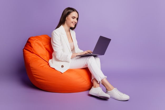 Close up profile portrait of positive lady sit beanbag hold computer typing on purple wall