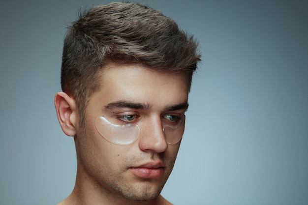 Close-up profile portrait of young man isolated on grey studio background. male face with collagen patches under eyes. concept of men's health and beauty, cosmetology, body and skin care. anti-aging.