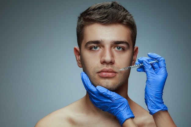 Close-up profile portrait of young man isolated on grey studio, filling surgery procedure