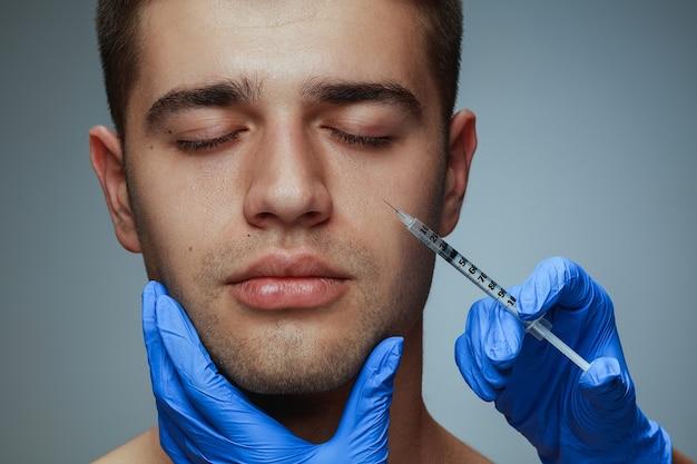 Ritratto di profilo del primo piano del giovane isolato su studio grigio, procedura di chirurgia di riempimento