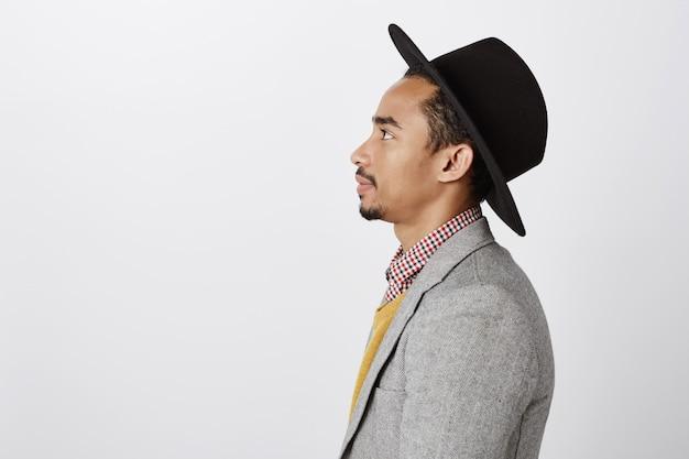 Colpo di profilo del primo piano del ragazzo hipster afroamericano bello in vestito e cappello che osserva a sinistra