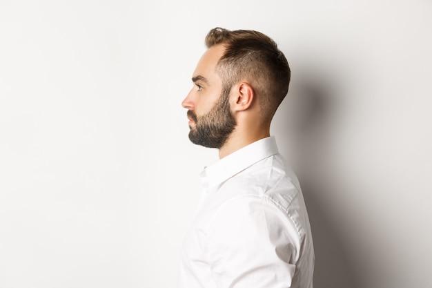 Close-up shot di profilo di bell'uomo barbuto guardando a sinistra, in piedi su sfondo bianco.