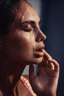 완벽한 관능적 인 입술로 화려한 섹시한 젊은 여성 모델의 프로필 샷을 닫고 그녀의 얼굴에 물 방울과 눈을 감았습니다.