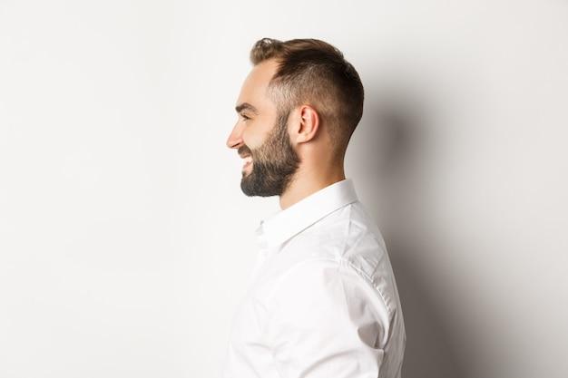 Крупным планом профиль красивый бородатый мужчина смотрит влево и улыбается, стоя на белом фоне.