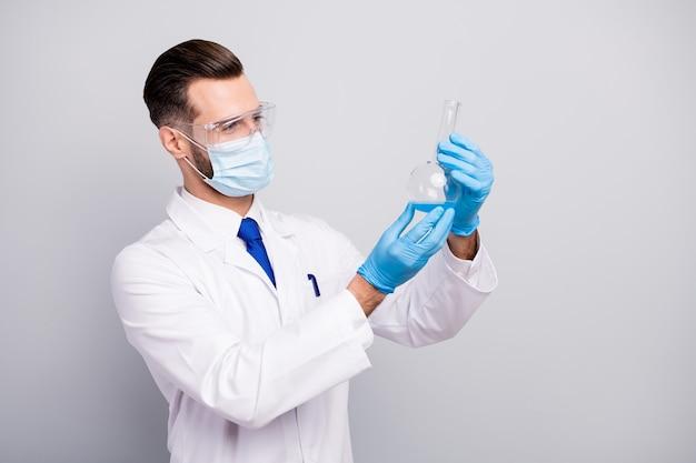 Боковой портрет крупным планом, его красивый привлекательный опытный опытный ученый-доктор, делающий аналитический лабораторный центр, держащий лампочку в руках, изолированные на светло-белом сером пастельном цвете