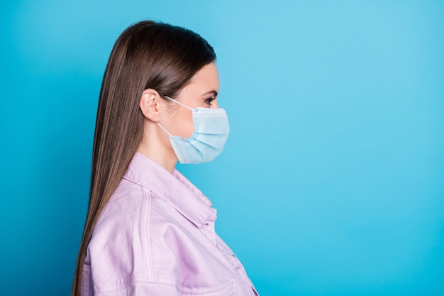Close-up profile side view portrait of her she attractive girl wearing gauze safety mask stop influenza flu grippe health care copy space isolated bright vivid shine vibrant blue color background