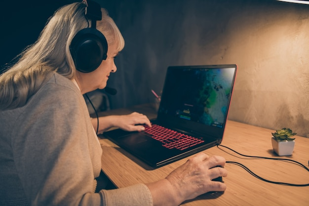 Close-up profile side view portrait of her she nice attractive addicted focused gray-haired blonde mother playing e-sport game spending day at industrial loft modern concrete style interior house