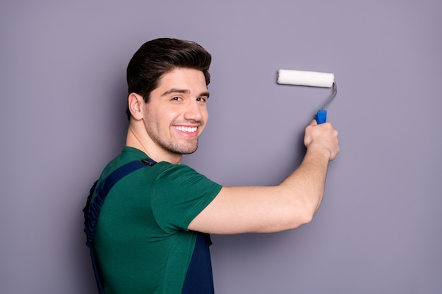 Close-up profile side view portrait of his he nice attractive brunette cheerful cheery guy making renovation restoration new design painting wall isolated over gray pastel color wall