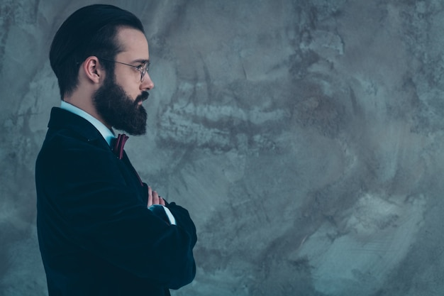 Close-up profile side view portrait of his he nice attractive representative serious bearded guy wearing velvet tux folded arms copy space isolated over gray concrete industrial wall