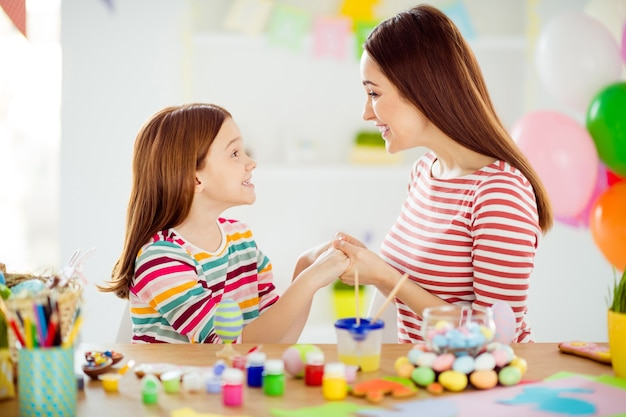 Close-up profile side view portrait of nice attractive lovely gentle sweet cheerful cheery girls small little daughter making handicraft spending day holding hands in white light interior room house