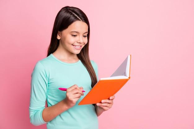 Крупный план профиля, вид сбоку, ее портрет, она милая, привлекательная, довольно сосредоточенная, веселая, веселая, длинноволосая, девушка, пишет задание на академический предмет, изолированное на розовом пастельном цветном фоне