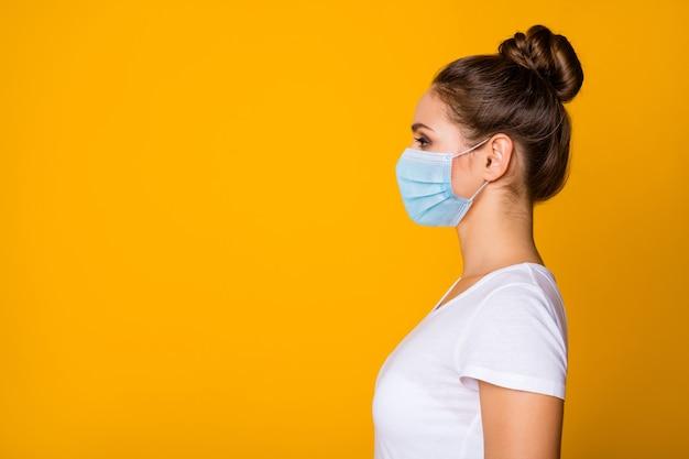 安全ガーゼマスクを身に着けている彼女の素敵な女の子のクローズアッププロファイル側面図の肖像画肺炎伝染性インフルエンザグリッペインフルエンザコピースペースプラカードポスター孤立した鮮やかな黄色の背景