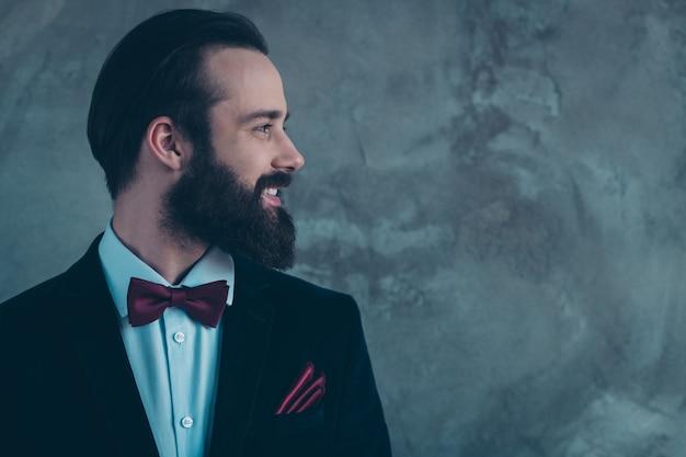 Крупный план профиля, вид сбоку, его красивый привлекательный стильный веселый веселый бородатый парень в смокинге для мероприятия, изолированный над серой бетонной промышленной стеной