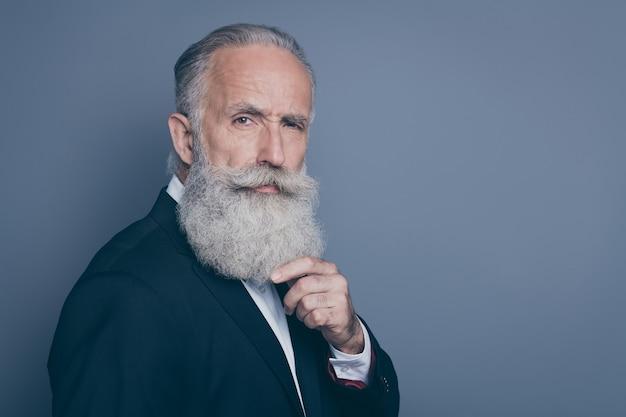 彼の素敵な魅力的な疑わしい手入れの行き届いた白髪の男マッチョモデルのクローズアッププロファイル側面図の肖像画灰色の紫紫パステルカラーの背景の上に分離されたひげに触れることを考えています