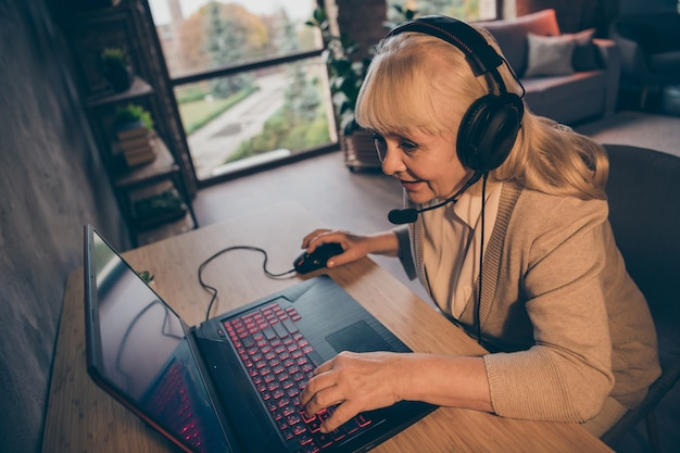 Профиль крупным планом, вид сбоку, портрет красивой привлекательной увлеченной веселой сосредоточенной седой блондинки-бабушки, играющей в командную киберспортивную игру vr на промышленном чердаке, современный бетонный кирпич в интерьере дома