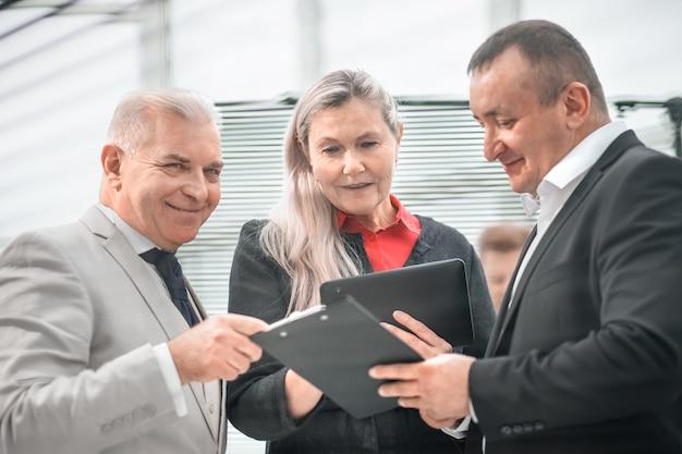 Закройте вверх. менеджер проекта обсуждает рабочие документы с коллегами