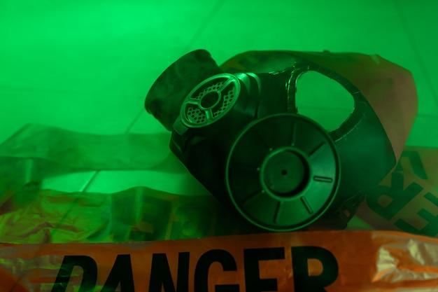 Крупный план: защитный противогаз и красная лента «опасность» лежат среди дыма на зеленом фоне. радиационная опасность.